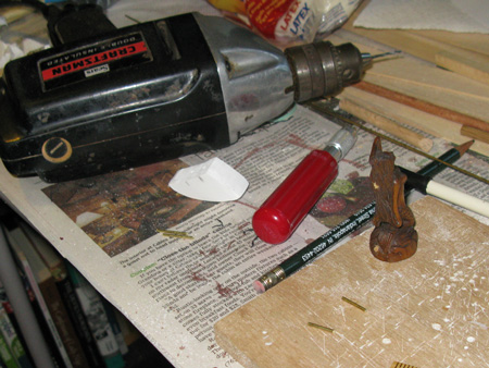 Basswood mermaid carving.  PVC trim board support piece.  7 brass rods.  KwikWeld epoxy.