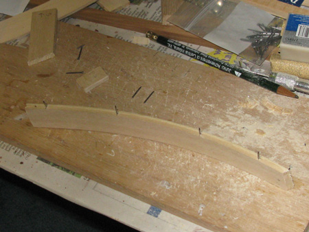 The forecastle rails were made from basswood strips, wood glue and cut nails.  I clamped them along the bow to get the right curve.