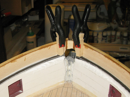 Knightheads clamped in place.  Pinned and epoxied to the fiberglass lip and wood-glued to the inside of the rail.